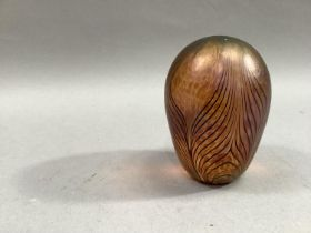 An iridescent glass paperweight, the amber mottled ground with swirled pattern, 11.5cm