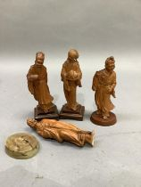 Four Chinese fruit wood carvings of deities, eached raised on a plinth, heights ranging from 15.