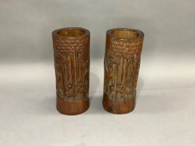 A pair of bamboo brush pots each carved in relief with figures amongst bamboo grove and pine