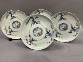 A set of four Japanese porcelain plates, each decorated to the centre with a stylised dragon, the