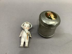 A Bisque figure of an infant with jointed arms and hat, 13.5cm high together with a metal musical