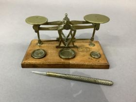 An Edwardian mahogany and brass set of postal scales with weights for 0.5oz, 1oz and 2oz together