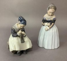 Two Royal Copenhagen figures of Dutch girls, one standing, the other sitting knitting, printed and