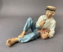 A Royal Copenhagen figure of a country boy resting as he eats his lunch, printed and underglaze blue