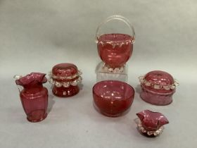 Six items of cranberry glass including two lidded jars with prunt rims together with a jug with