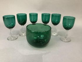 A set of six emerald green glass wines and an emerald green glass finger bowl, the latter 9cm high