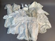 Four Edwardian baby's dresses in fine cotton with embroidered, lace and drawn thread work, a bib,