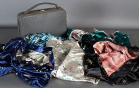 Two Far Eastern style dresses and two skirts in embroidered silk and a lady's travel case