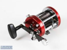 ABU Ambassadeur 7000 multiplier reel stamped 821000 to base, finished in red, runs smooth, signs