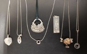 SEVEN VARIOUS SILVER PENDANTS including an ingot pendant with decorative hallmarks, 29.4 grams; a