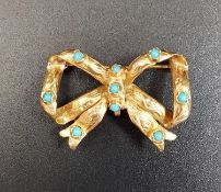 TURQUOISE SET BOW SHAPED GOLD BROOCH in unmarked high carat gold, approximately 3.3cm wide and 4.5