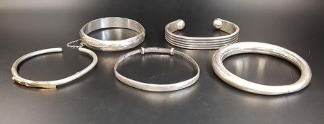FIVE SILVER BANGLES comprising one with nine carat gold detail; a Japanese Meiji Period expanding