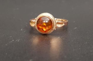 RUSSIAN AMBER SET RING the central round cabochon amber on fourteen carat rose gold shank with