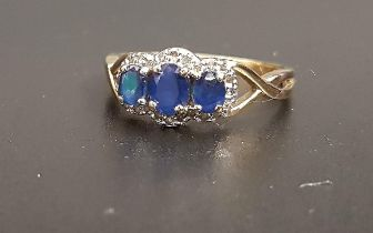 SAPPHIRE AND DIAMOND RING the three graduated oval cut sapphires in diamond surround, on nine