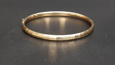 NINE CARAT GOLD HINGED BANGLE with multifaceted decorative surface detail and extending slider