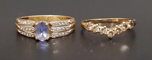 BLUE GEM AND DIAMOND DRESS RING the central oval cut blue gemstone flanked by three rows of diamonds