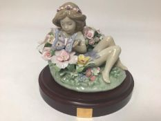 A Lladro porcelain figure of a recumbent sprite amongst flowers holding a butterfly, 'Sprite No.