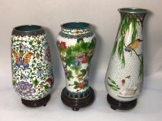 Three various large cloisonné enamel vases on stands, decorated with flowers, birds and