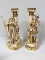 A pair of Royal Dux porcelain figures of a shepherd and shepherdess modelled next to classical Ionic