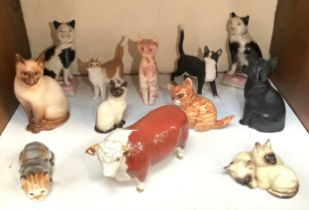 A collection of 11 various ceramic, composite and stone model cats including some Royal Doulton