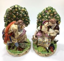 A pair of early 19th century Derby porcelain 'bocage' figure groups, each modelled with courting