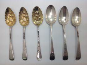 A pair of George III silver and silver-gilt berry spoons, London, 1810, together with another