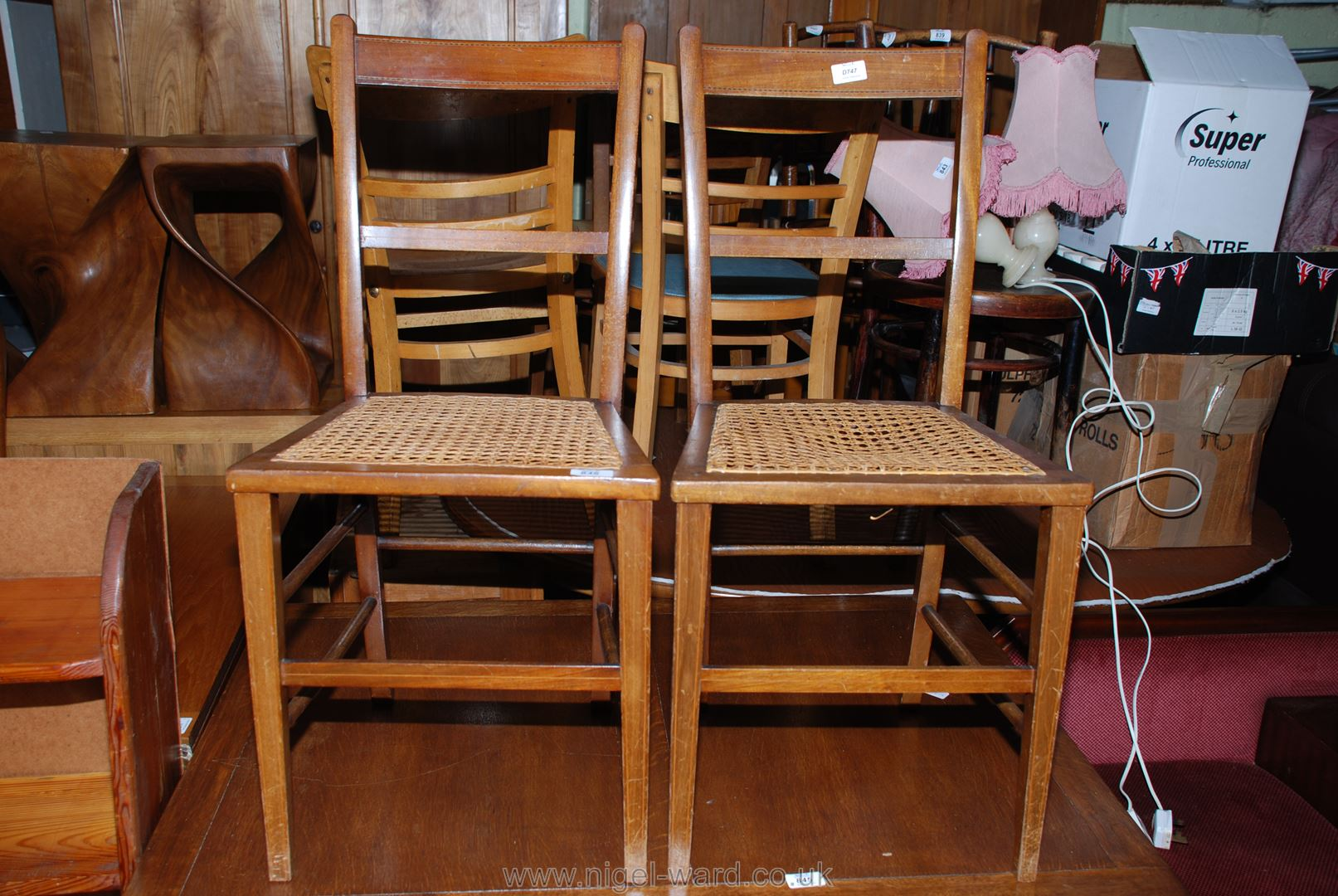 A pair of cane seated ladder back chairs.