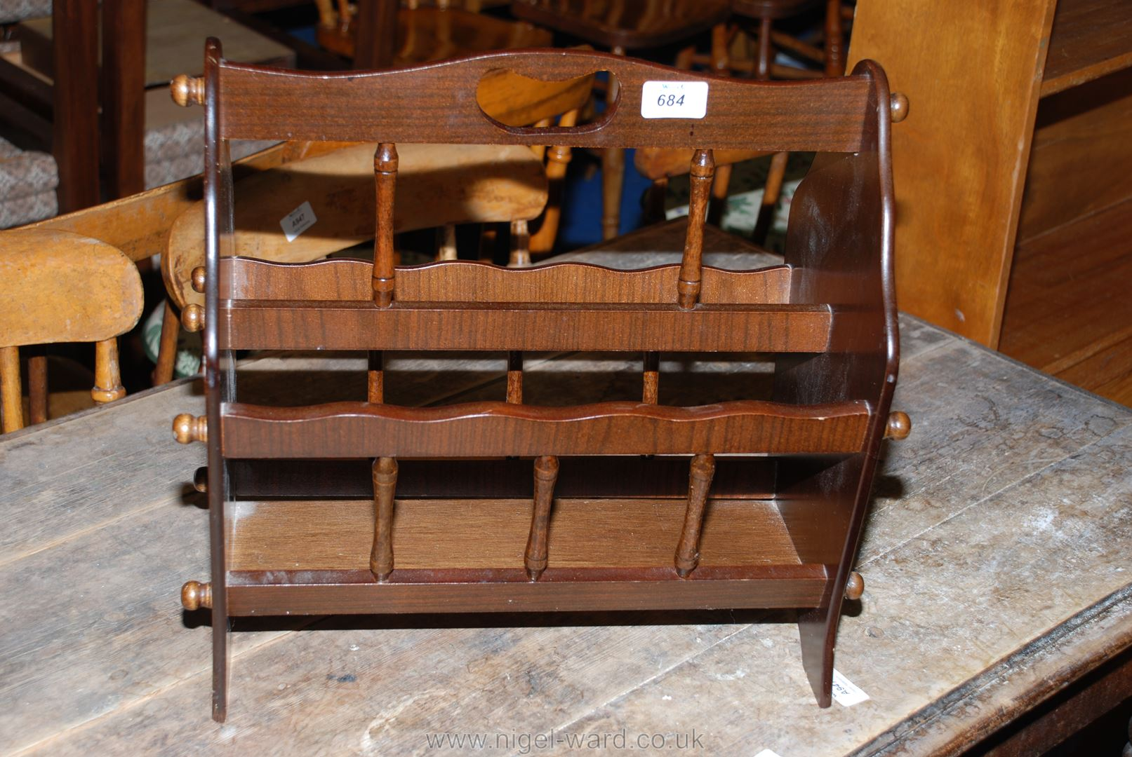 A dark-wood finished two-compartment magazine rack.