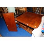 A Satinwood extending dining table standing on turned legs and with an extra leaf,