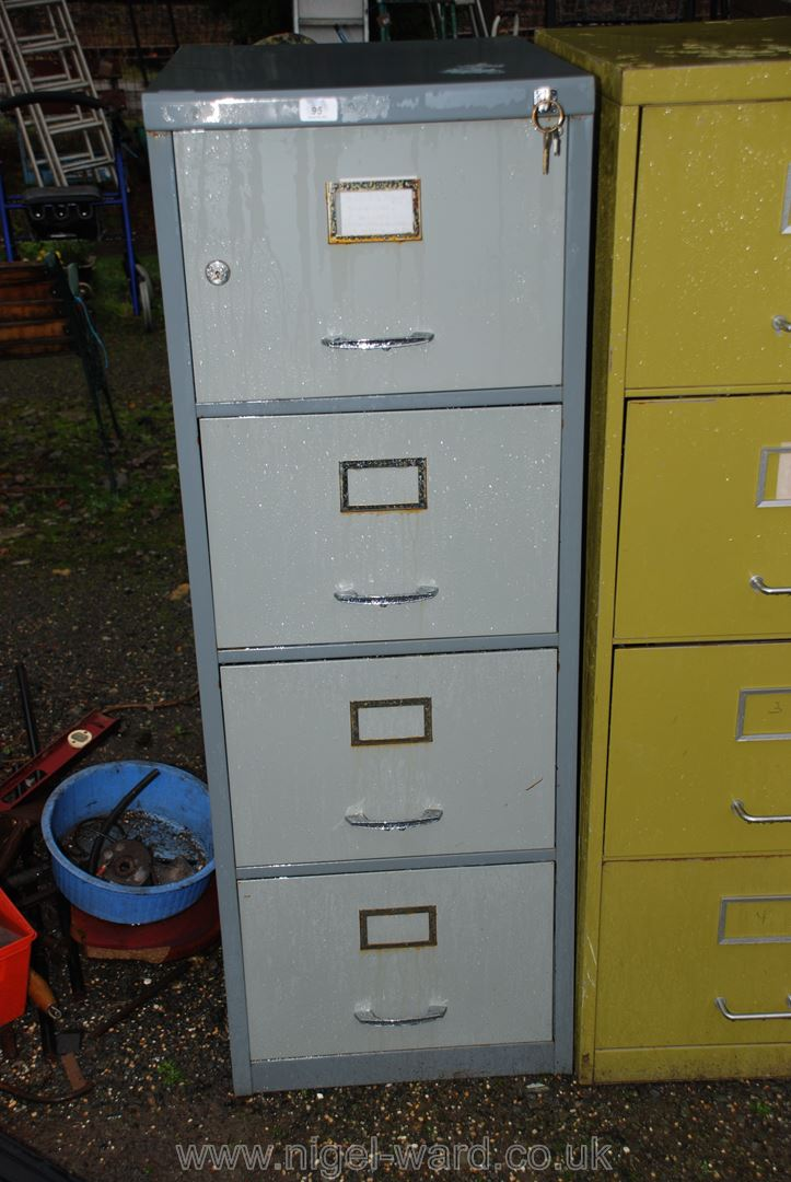 A three drawer filing cabinet with top cupboard (with key).
