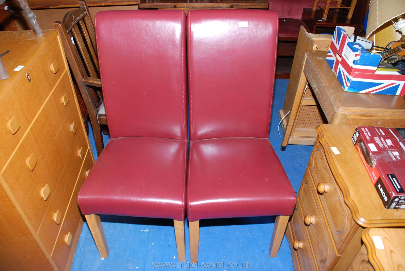 A pair of leather effect dining chairs.