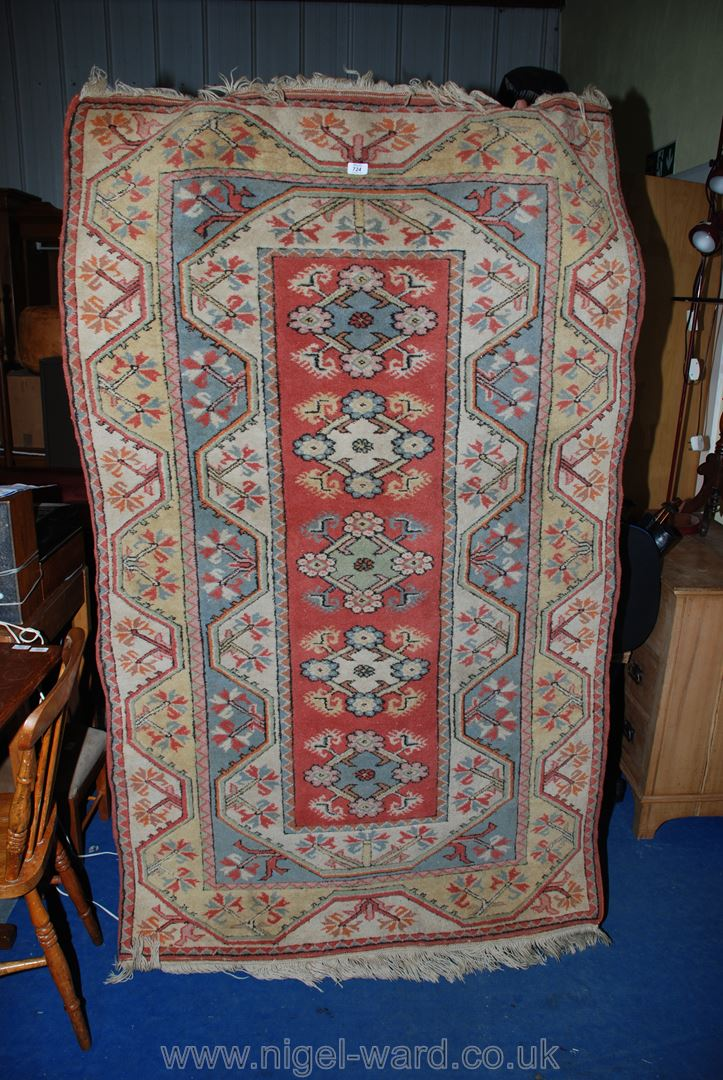 """A bordered, patterned and fringed rug with a geometric and lozenge design, 47"""" x 78""""."""