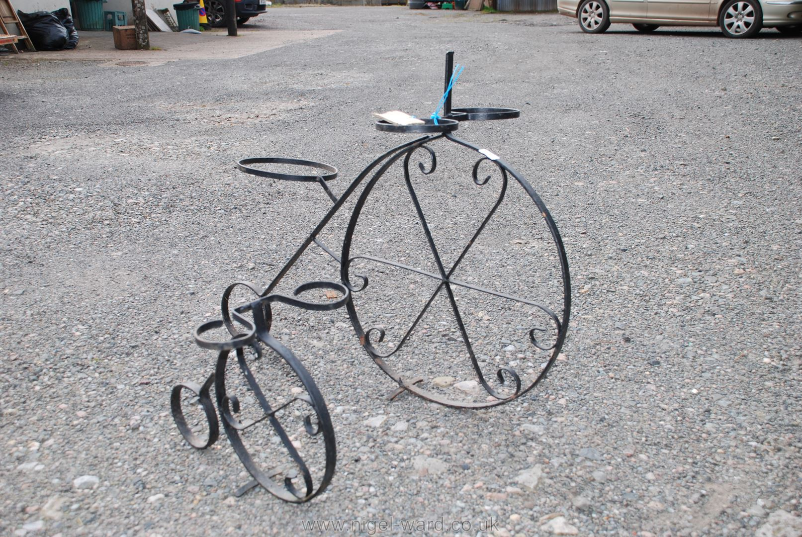 Two wrought iron plant stands in the form of penny farthings, largest 28'' x 33''.