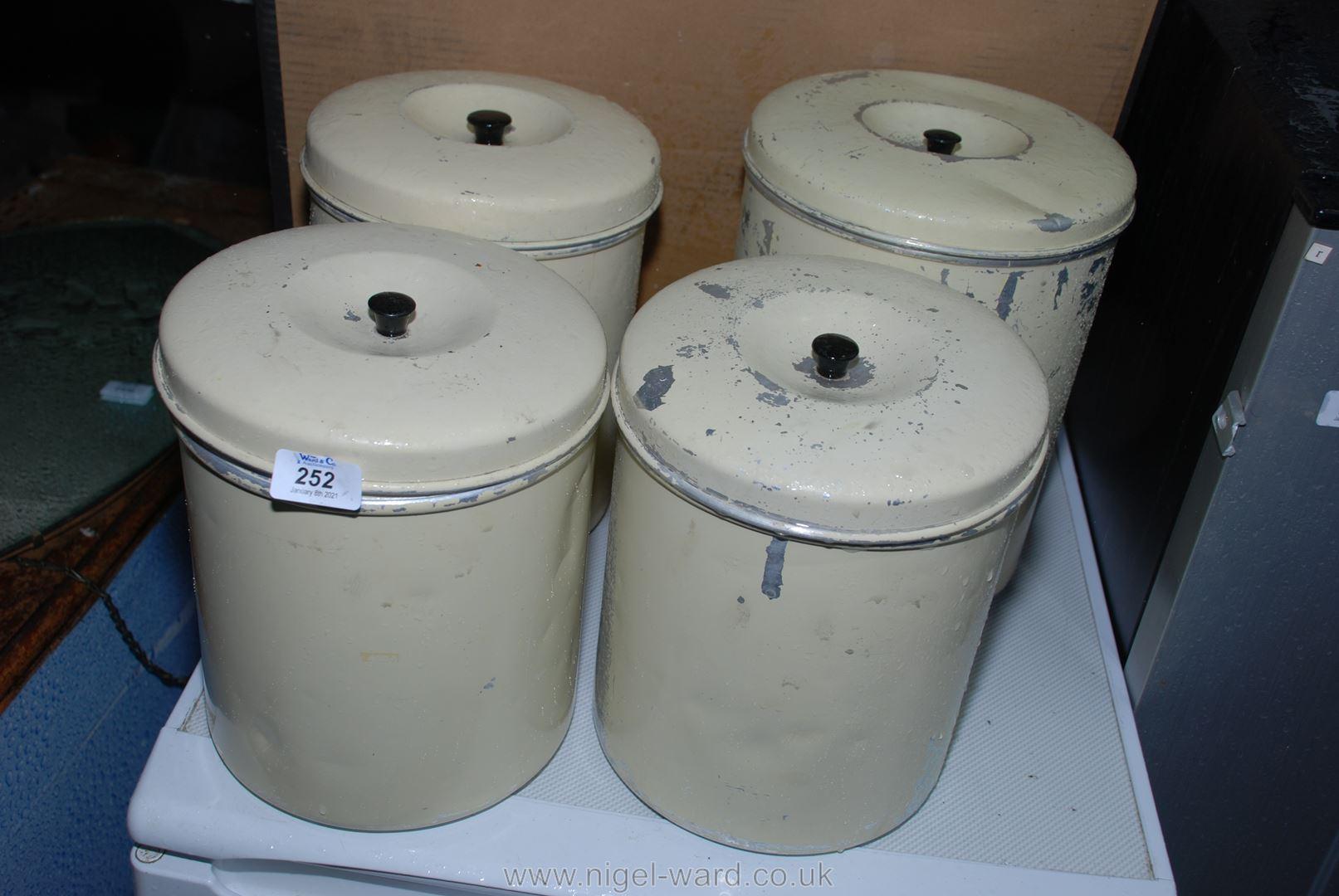 Four painted aluminium kitchen storage pots with lids.