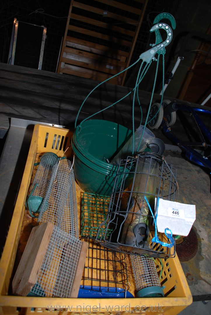 A quantity of various bird feeders and hanging baskets.