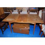 A pull-out Mahogany finished 1960's design dining table with fold-out central leaf,
