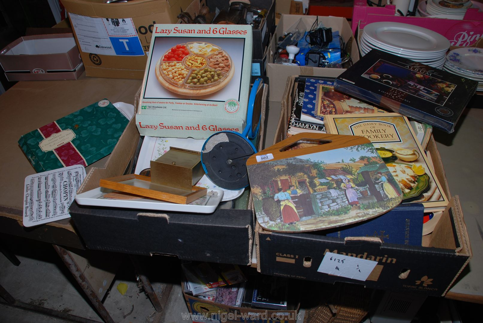Two boxes of cookery books, trays, a lazy Susan, place mats, etc.