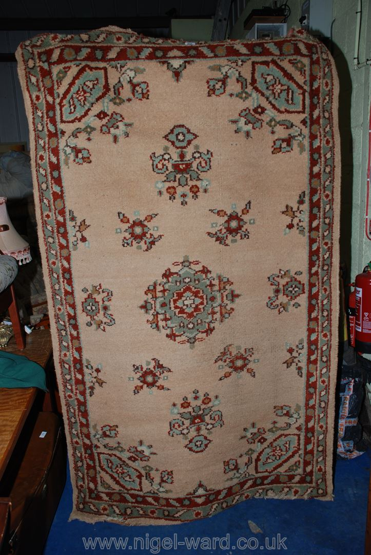 """A bordered and patterned rug in red and beige, 81"""" x 49"""" approx."""