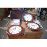Four wall clocks and a wooden tray.