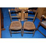 A pair of cane seated bedroom chairs.