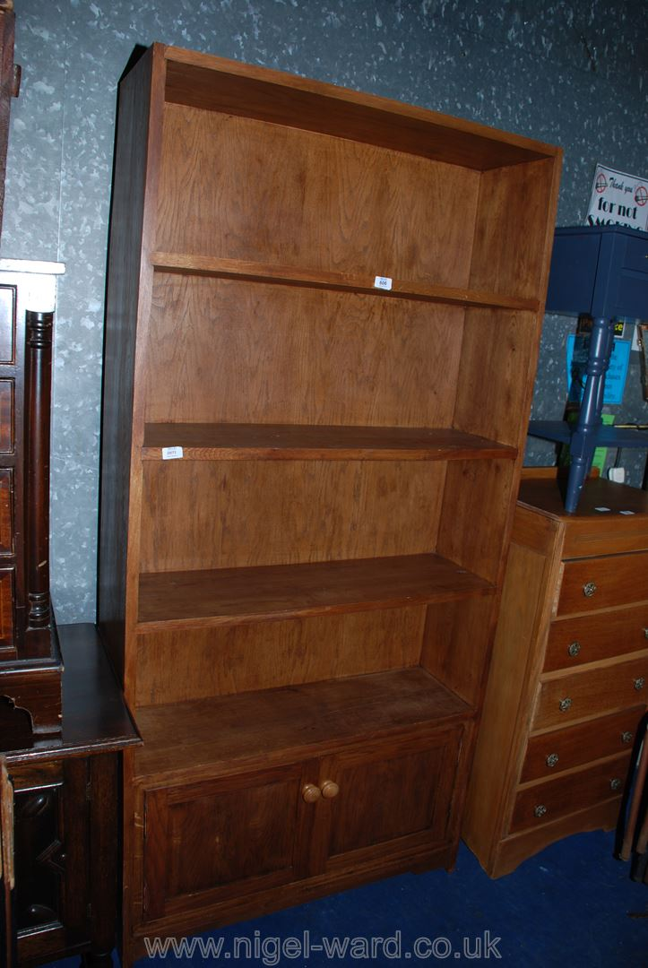 """A Satinwood four-shelf unit over two-doored cupboard base, 37"""" x 76"""" x 11"""" deep."""