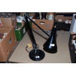 A black angle-poise lamp.