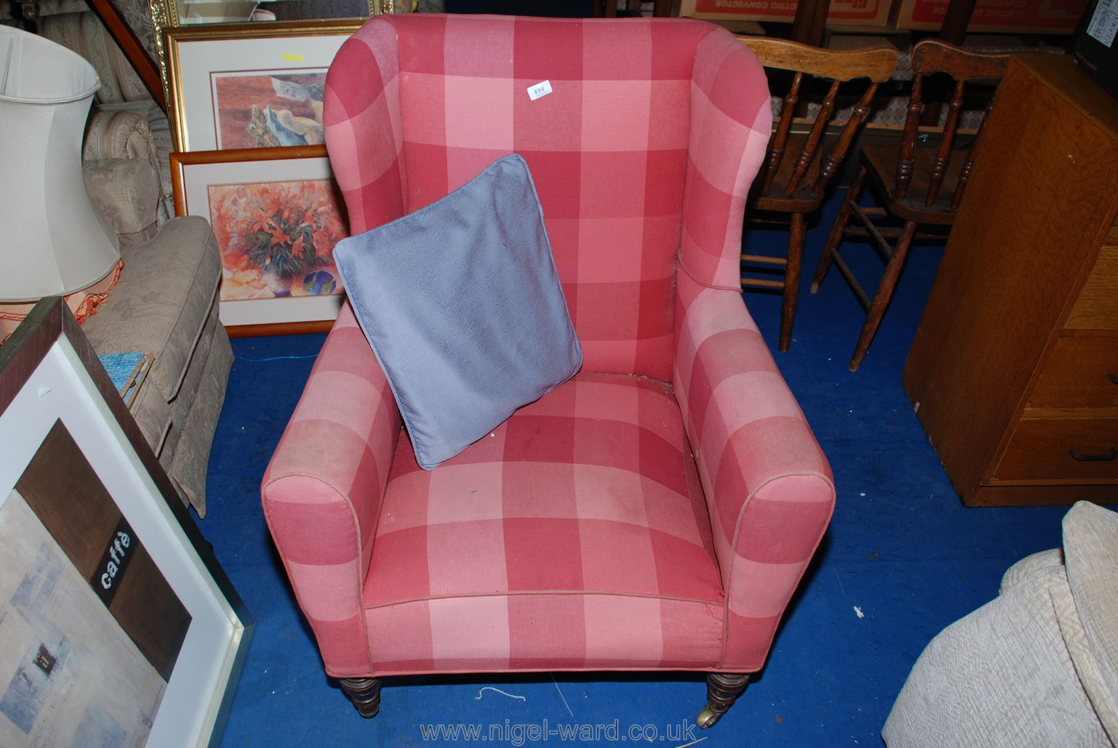 A pink check-upholstered wingback armchair.