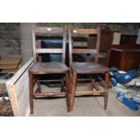 A pair of wooden kitchen chairs.