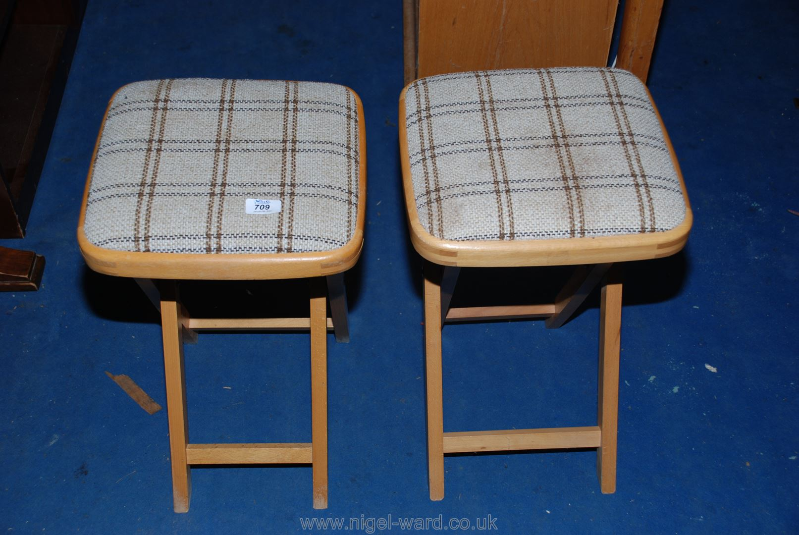 Two check-upholstered folding stools.