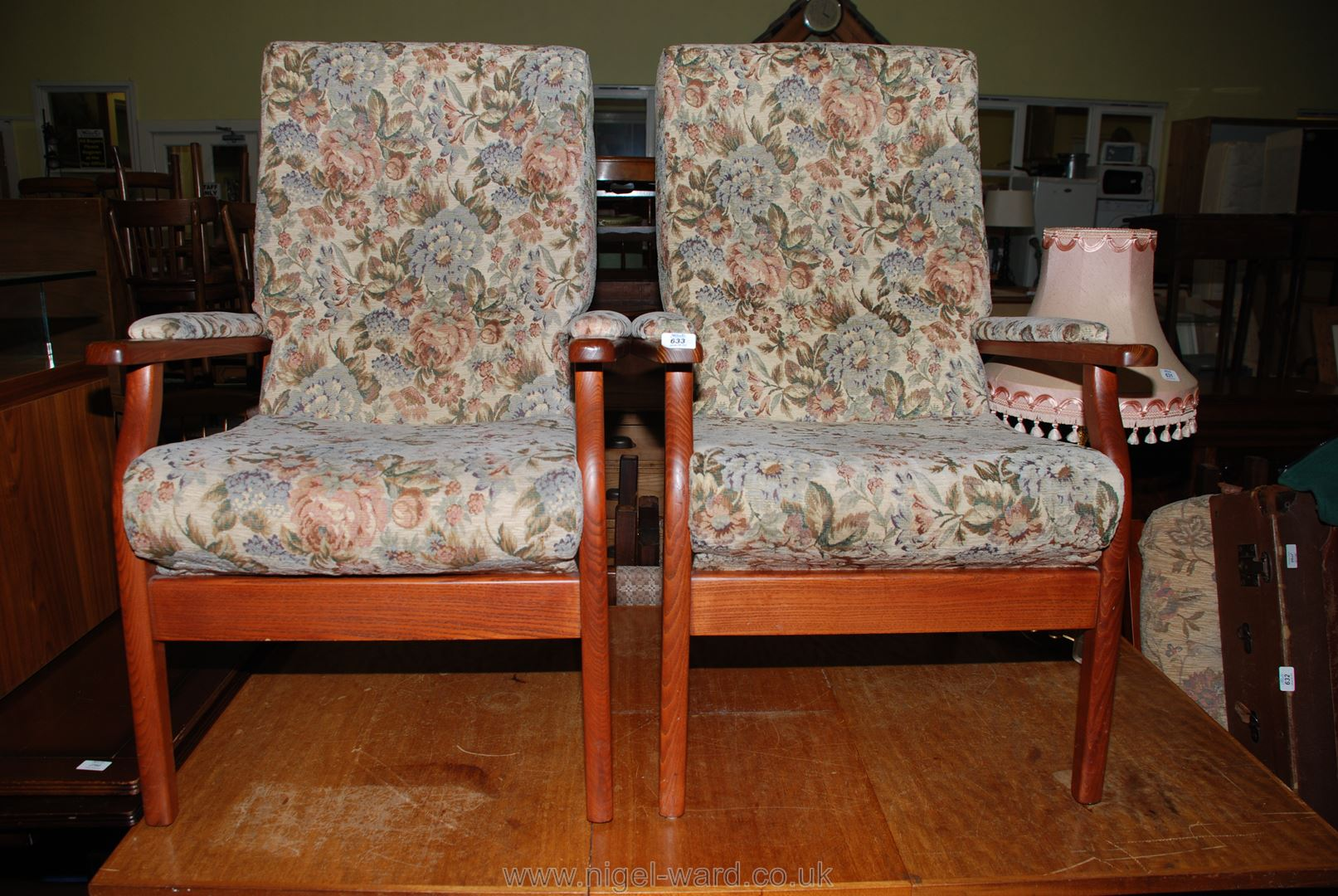 A pair of floral upholstered open-armed armchairs.