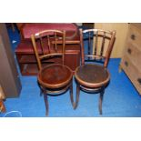 A pair of circular seated cafe type bent-wood chairs.