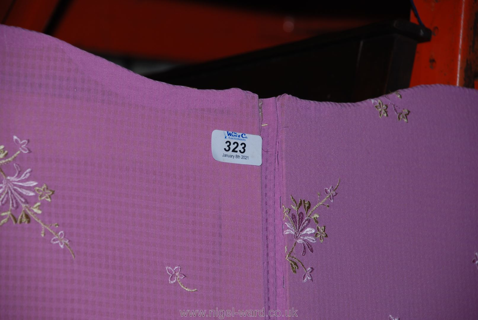 A three-fold dressing screen with scalloped top and pink ground floral decorated upholstery,