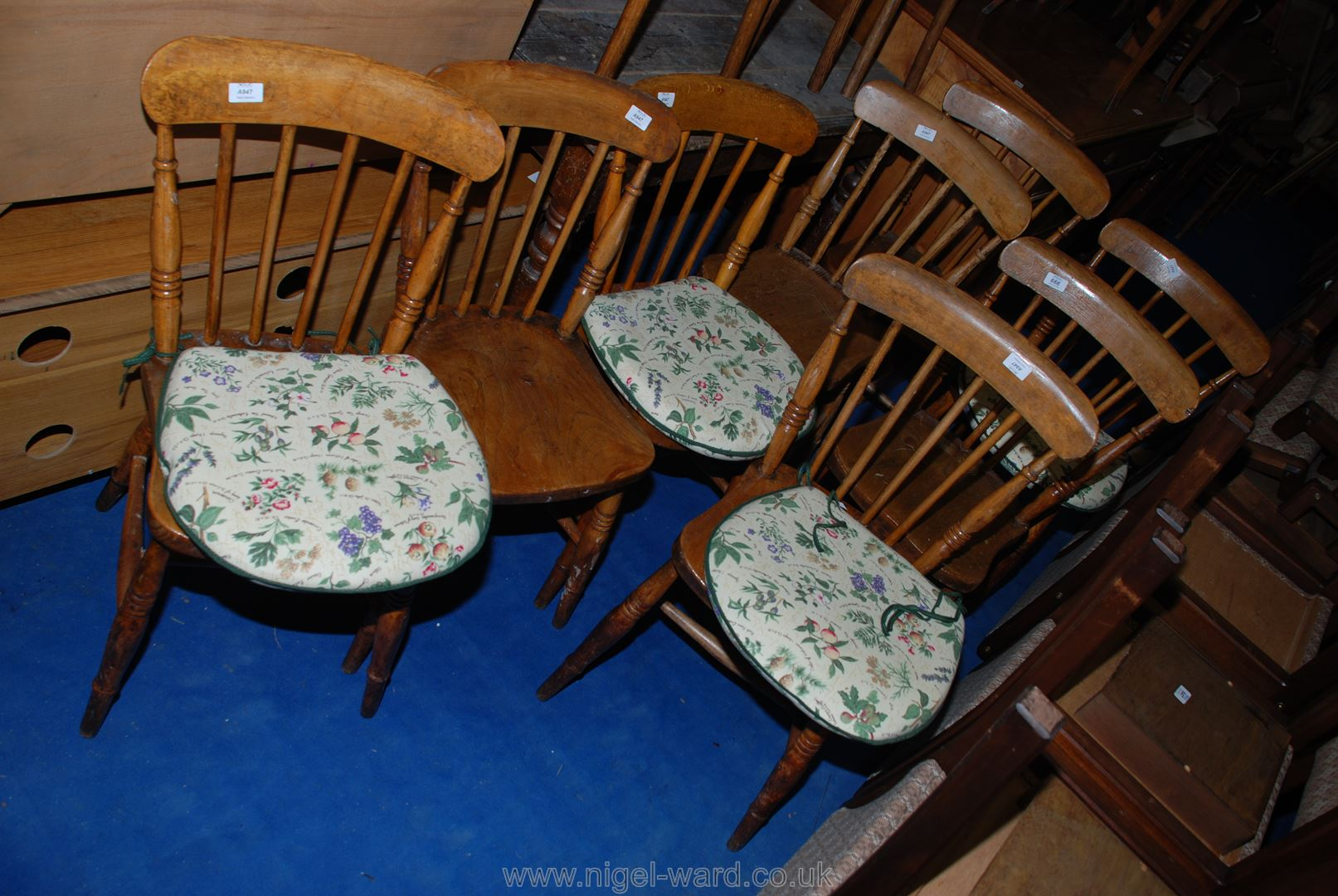 A set of eight solid Elm seated stick-back kitchen chairs, some having padded cushions.