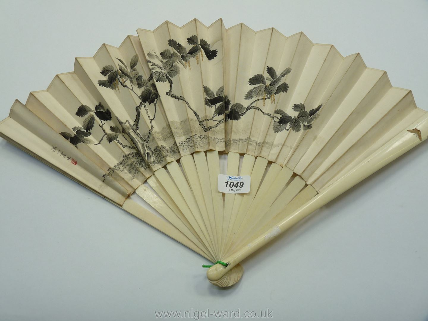 A Japanese painted silk Fan with signatures and red seal marks, the sticks inlaid with coral,
